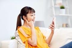 Mujer asiática feliz con smartphone y los auriculares Fotos de archivo