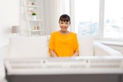 Mujer asiática feliz con ver la TV en casa Imagenes de archivo