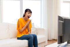 Mujer asiática feliz con ver la TV en casa Imagen de archivo