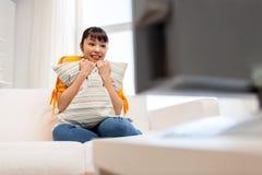 Mujer asiática feliz con ver la TV en casa Fotografía de archivo libre de regalías