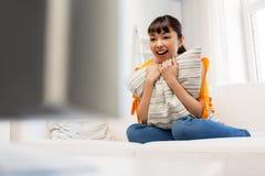 Mujer asiática feliz con ver la TV en casa Imagen de archivo libre de regalías