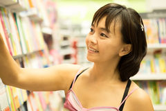 Mujer asiática feliz de elegir un poco de libro en el estante fotos de archivo libres de regalías