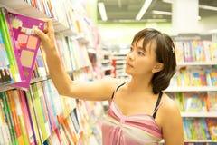 Mujer asiática feliz de elegir un poco de libro en el estante fotos de archivo