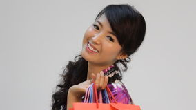 Mujer asiática feliz de las compras que sonríe y que sostiene los panieres almacen de metraje de vídeo