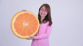 Mujer asiática feliz joven del empollón con la almohada anaranjada como concepto sano almacen de metraje de vídeo