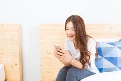Mujer asiática feliz joven que usa su teléfono elegante en su dormitorio Fotos de archivo libres de regalías