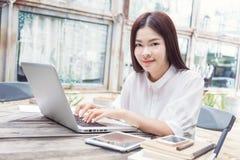 Mujer asiática feliz joven que usa tecnología en su ordenador portátil Imagenes de archivo