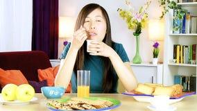 Mujer asiática feliz que come el yogur blanco metrajes