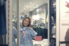 Mujer asiática feliz que elige la ropa y que mira para duplicar en tienda de la alameda o de ropa Fotos de archivo libres de regalías