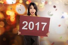 Mujer asiática feliz que lleva a cabo el número 2017 en el tablero rojo Fotos de archivo libres de regalías