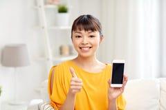Mujer asiática feliz que muestra smartphone en casa Fotos de archivo libres de regalías