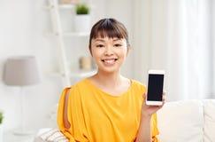 Mujer asiática feliz que muestra smartphone en casa Fotografía de archivo libre de regalías