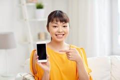 Mujer asiática feliz que muestra smartphone en casa Fotografía de archivo