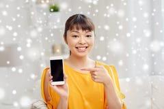 Mujer asiática feliz que muestra smartphone en casa Imagen de archivo