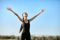 Mujer asiática feliz que se coloca con los brazos abiertos para encontrar el sol Fotografía de archivo libre de regalías