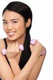 Mujer asiática feliz que se resuelve con pesas de gimnasia Imágenes de archivo libres de regalías