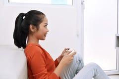 Mujer asiática feliz que se sienta en el piso y que juega a los videojuegos Fotografía de archivo libre de regalías