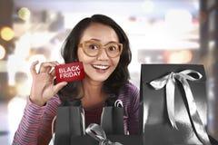 Mujer asiática feliz que sostiene la tarjeta con Black Friday Fotos de archivo