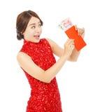 Mujer asiática feliz que sostiene un sobre rojo con el dinero Imagen de archivo