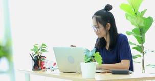 Mujer asiática feliz que trabaja en el ordenador portátil con la cara de la sonrisa El hacer compras en línea con de la tarjeta d almacen de video