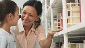 Mujer asiática feliz y sus pequeños libros de la cosecha de la hija de un estante almacen de metraje de vídeo