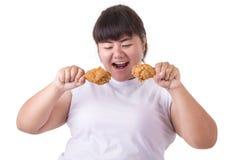 Mujer asiática gorda que sostiene y que come el pollo frito aislado en whi Foto de archivo