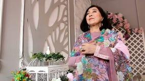 Mujer asiática hermosa adulta en soporte hermoso del vestido de noche en el cuarto floral almacen de video