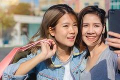 Mujer asiática hermosa atractiva que usa un smartphone mientras que hace compras en la ciudad Adolescente asiático joven feliz en Foto de archivo