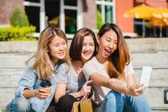 Mujer asiática hermosa atractiva que usa un smartphone mientras que hace compras en la ciudad Adolescente asiático joven feliz en Fotografía de archivo libre de regalías