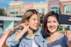 Mujer asiática hermosa atractiva que usa un smartphone mientras que hace compras en la ciudad Adolescente asiático joven feliz en Imagenes de archivo