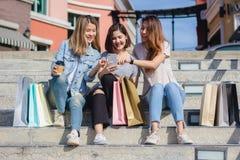 Mujer asiática hermosa atractiva que usa un smartphone mientras que hace compras en la ciudad Adolescente asiático joven feliz en Fotografía de archivo