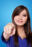 Mujer asiática hermosa con el finger acentuado, en fondo azul Fotografía de archivo