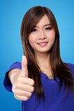 Mujer asiática hermosa con el pulgar para arriba, en fondo azul Imagenes de archivo