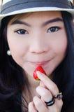 Mujer asiática hermosa con la fresa Imagenes de archivo