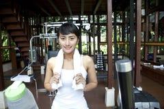 Mujer asiática hermosa con la toalla que presenta en gimnasia Imagenes de archivo