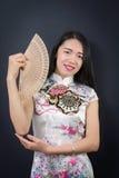 Mujer asiática hermosa con una fan de la mano Imágenes de archivo libres de regalías