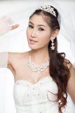 Mujer asiática hermosa del retrato en el vestido de boda blanco con velo Imagen de archivo libre de regalías