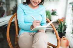 Mujer asiática hermosa en casa que escribe y que trabaja con el diario Imagenes de archivo