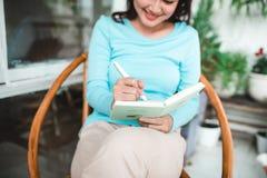 Mujer asiática hermosa en casa que escribe y que trabaja con el diario Imágenes de archivo libres de regalías