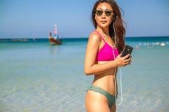 Mujer asiática hermosa feliz que escucha la música en la playa cerca de orilla de mar fotografía de archivo libre de regalías