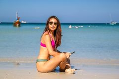 Mujer asiática hermosa feliz que escucha la música en la playa cerca de orilla de mar fotos de archivo