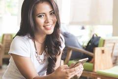 Mujer asiática hermosa joven en un restaurante, sosteniendo el teléfono móvil Imágenes de archivo libres de regalías