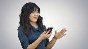 Mujer asiática hermosa joven positiva que usa el teléfono móvil, el baile y la sonrisa en el fondo blanco almacen de metraje de vídeo