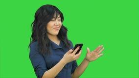 Mujer asiática hermosa joven positiva que usa el teléfono móvil, el baile y la sonrisa en una pantalla verde, llave de la croma almacen de video