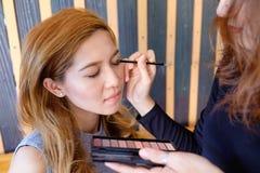 Mujer asiática hermosa joven que aplica maquillaje Foto de archivo