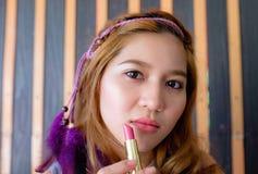 Mujer asiática hermosa joven que aplica maquillaje Fotos de archivo libres de regalías