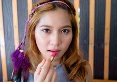 Mujer asiática hermosa joven que aplica maquillaje Imágenes de archivo libres de regalías