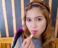 Mujer asiática hermosa joven que aplica maquillaje Foto de archivo libre de regalías