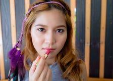 Mujer asiática hermosa joven que aplica maquillaje Imagen de archivo libre de regalías