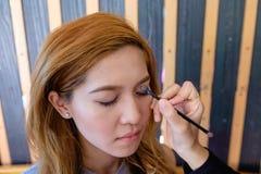 Mujer asiática hermosa joven que aplica maquillaje imagenes de archivo